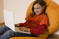 Young Girl With Laptop. Nine year old girl sitting on a beanbag working on a laptop Stock Photography