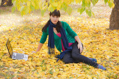 Young girl with a laptop in a autumn foliage Stock Images