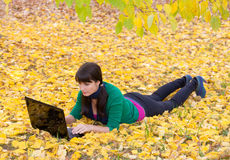Young girl with a laptop in a autumn foliage Stock Photo