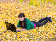 Young girl with a laptop in a autumn foliage Royalty Free Stock Photography