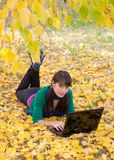Young girl with a laptop in a autumn foliage Stock Image