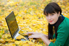 Young girl with a laptop in a autumn foliage Stock Photography