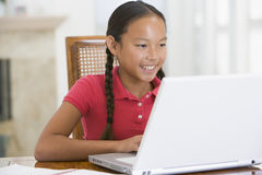 Young girl with laptop in dining room Royalty Free Stock Image