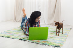 Young girl with laptop and dog Stock Images