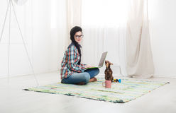 Young girl with laptop and dog Stock Image