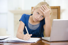 Young girl with laptop doing homework Royalty Free Stock Image