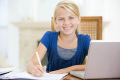 Young girl with laptop doing homework. In dining room stock photos