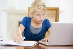 Young girl with laptop doing homework Stock Images