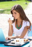Young girl with laptop drinking coffee Royalty Free Stock Photography