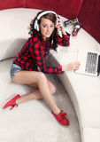 Young girl with laptop listen to music Stock Image