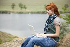 Young girl with laptop at rock near lake Royalty Free Stock Photography