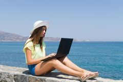 Young girl with laptop, in shorts and white hat Stock Photos