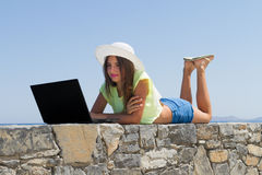 Young girl with laptop, in shorts and white hat Stock Photo