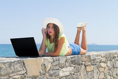 Young girl with laptop, in shorts and white hat Royalty Free Stock Images
