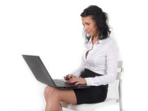 Young girl with a laptop sitting. On a chair, looking for information, working Stock Photo