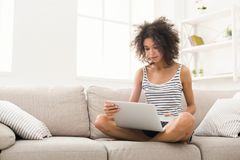 Young girl with laptop sitting on beige couch. Young african-american woman working on laptop sitting on beige couch, surfing net, copy space Stock Image