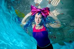 Young girl with large bow clown on the head swims in the pool underwater and looking at the camera. Portrait. Horizontal view. Vie. W from the bottom Royalty Free Stock Image