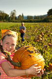 Young girl with large pumpkin, in field. Young girl in field holding large pumpkin, boy behind Stock Photo