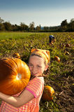 Young girl with large pumpkin, in field. Young girl in field holding large pumpkin, boy behind Stock Image