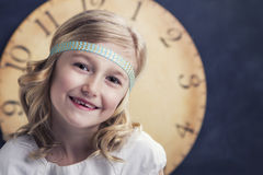 Young girl with large vintage clock Stock Images