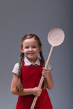 Young girl with  large wooden spoon Stock Photography