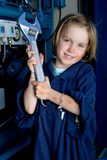 Young girl with large wrench. Portrait of a cute young girl, dressed in an oversized shirt and dirt on her face, holding a very large wrench stock images
