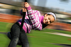 A young girl laughing happily as she rides on the playground pole. On a warm day Stock Images
