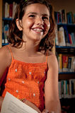 Young girl laughing in a library. A little girl reading in a library, taking some time off to laugh royalty free stock photos