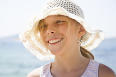 Young girl laughs in sun hat in sunshine Stock Image