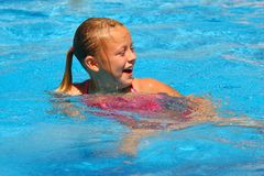 Young Girl Laughs in Swimming Pool. Young blond girl with pony tail laughs in a brilliant blue swimming pool Royalty Free Stock Photos