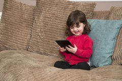 Young girl laughs at tablet royalty free stock photo
