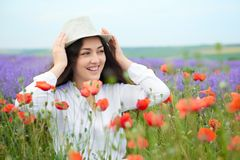 Young girl is in the lavender field, beautiful summer landscape with red poppy flowers Stock Images