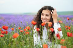 Young girl is in the lavender field, beautiful summer landscape with red poppy flowers Stock Photo