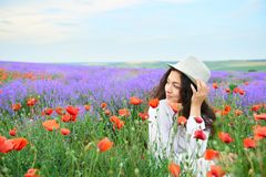 Young girl is in the lavender field with red poppy flowers, beautiful summer landscape Stock Photo