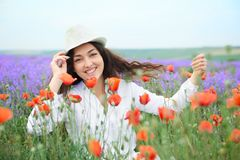Young girl is in the lavender field with red poppy flowers, beautiful summer landscape Stock Image
