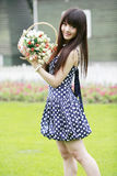 Young girl on the lawn. Young Asian girl holding a basket of flowers standing on the lawn Royalty Free Stock Images