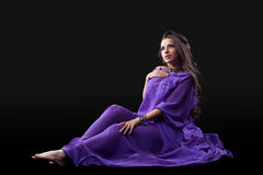 Young girl lay in purple traditional costume Stock Photos