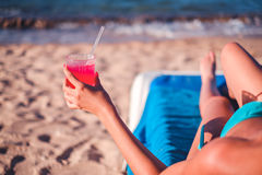 Young girl laying on the beach and holding cocktail Stock Photos