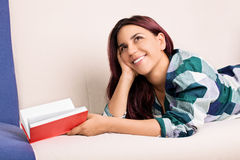 Young girl laying on a bed daydreaming while reading a book royalty free stock image