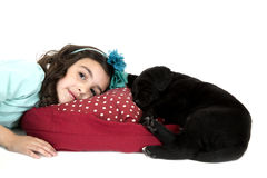 Young girl laying down by black puppy dog Royalty Free Stock Photography