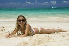Young girl laying down on white sandy beach. Stock Images