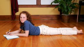 Young girl laying on the floor writing Royalty Free Stock Image