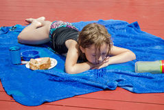Young girl laying out in the sun on a blue blanket Royalty Free Stock Photo