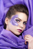Young girl laying on purple fabric Stock Photos