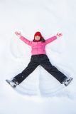 Young girl laying on snow and making angel. Stock Photos