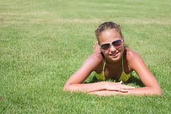 Young girl lays on a grass Royalty Free Stock Images
