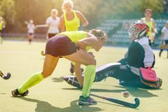 Young girl lead the ball into net in hockey match. Young girl lead the ball into the net behind goalier in field hockey match stock image