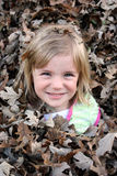 Young Girl in Leaf Pile Royalty Free Stock Photography