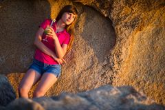 Young girl leaned against a stone wall at sunset with a cocktail in her hand royalty free stock images