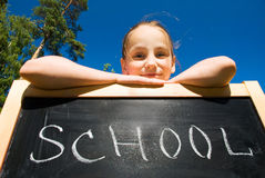 Young girl leaning against slate. With a writing school on it Stock Image